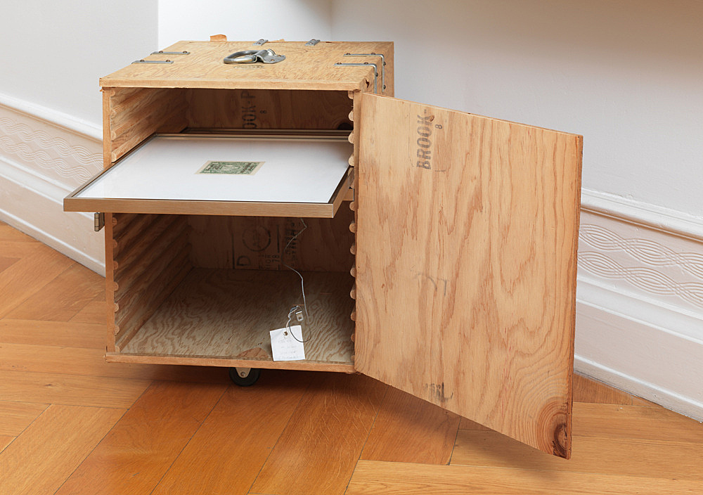 """– object from the estate of Martin Wong wooden box on wheels with metallic hinges and golden sticker """"Martin Wong – Human Instamatic – I M U – U R 2"""" 39 x 53 x 47 cm"""