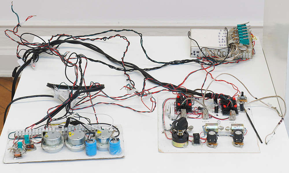 "Tony Conrad – ""Ten-channel Analog Audio Synthesizer"", 2009 plastic photo frame, electrical wires, tuning knobs, cables dimensions variable"