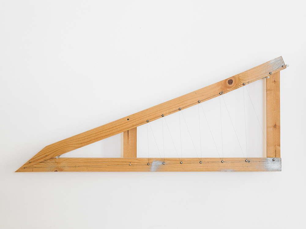 "Tony Conrad – ""Equal Tempered Twelve-tone Mesolabe"", ca. 2002 wood, rubber band, wire, tuning key, woven tie, screws 54 x 130 x 4,5 cm"