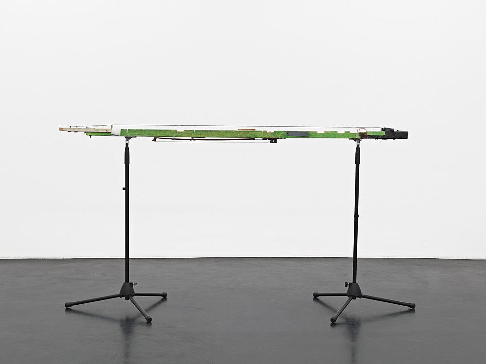 "Tony Conrad – ""Long String Drone"", 1972 wood, bass strings, electric pickup, tuning keys, tape, tuber band, metal hardware 7,5 x 187 x 8,5 cm"