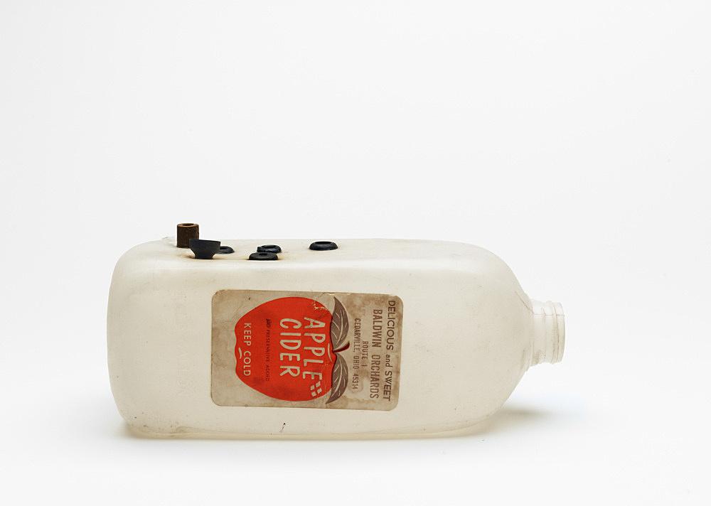 "Tony Conrad – ""Grommet Horn"", 1970 plastic bottle, rubber grommets 10,1 x 10,1 x 17,8 cm"