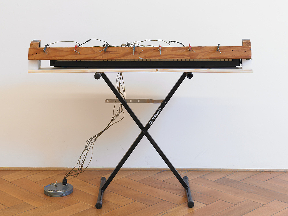 "Tony Conrad – ""Piano Vorsetzer"", 1979 piano, piano stand, clamps, electrical components, wooden bars, tape 96 x 134 x 45 cm"