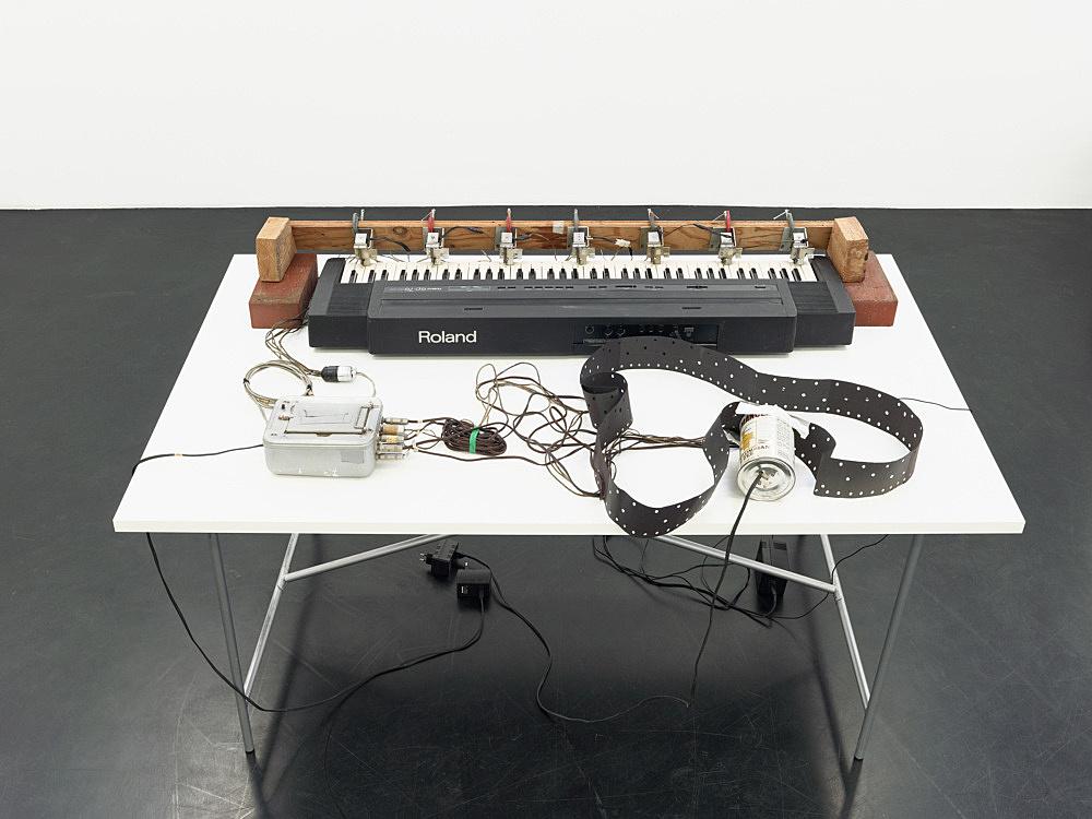"Tony Conrad – ""Piano Vorsetzer"", 1979 piano, clamps, electrical components, wooden bars, tape, program reader, punched paper software program 96 x 134 x 45 cm"