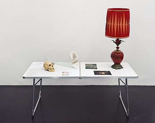 """Cheyney Thompson – """"Table Displaying Gifts from the Landlord and Working Papers"""", 2006 table, lamp, 4 computer printouts, xeroxed text with handwritten insertions, skull, glass, postcards, ventilator 174 x 184 x 76,5 cm"""