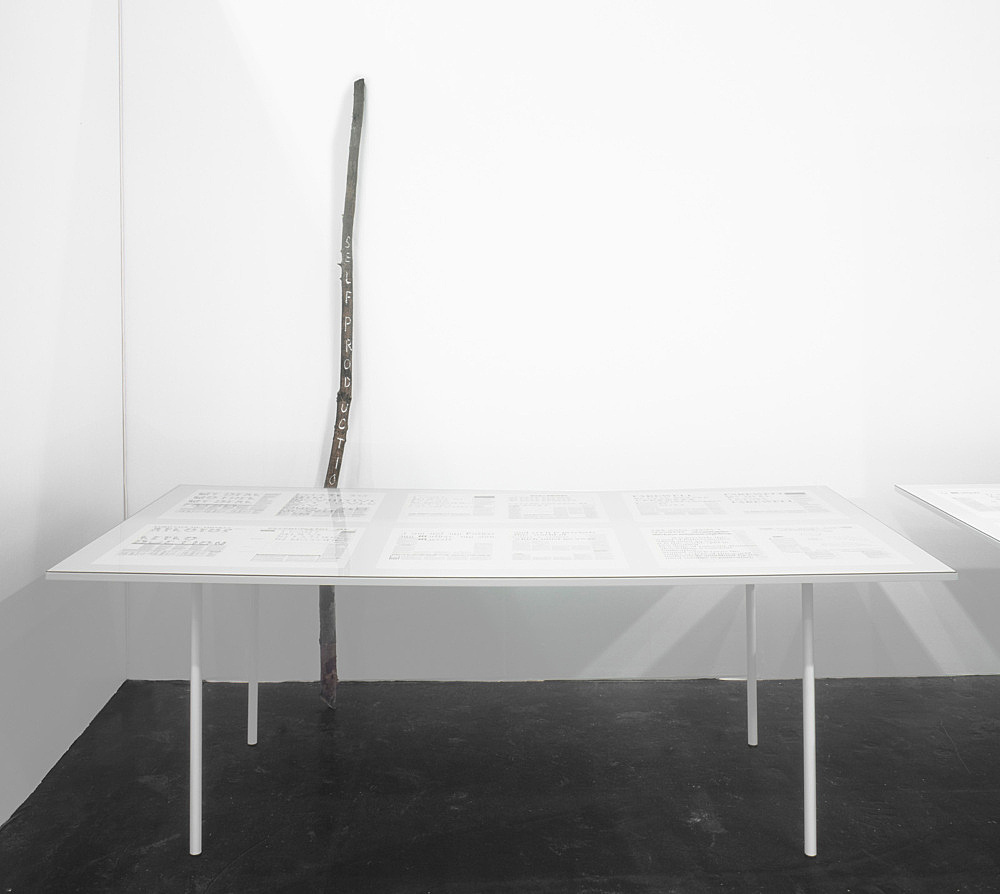 "Henrik Olesen – ""Self-production"", 2009 branch, edding, nails height: 234 cm & ""Papa-mama-Ich"", 2009 36 computer printouts on newsprint, each 48 x 33 cm 3 tables, each 83 x 230 x 120 cm glass detail"