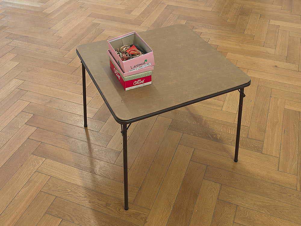 """Richard Hawkins – """"Scalps 11/12 (Remember the wonderful days when """"agency"""" sprung from """"alterity""""?)"""", 2011 rubber masks, painted paper, paperclips and shoeboxes on card table table: 70 x 86,5 x 86,5 cm boxes: 9,5 x 17 x 28 cm; 12 x 20 x 28 cm"""