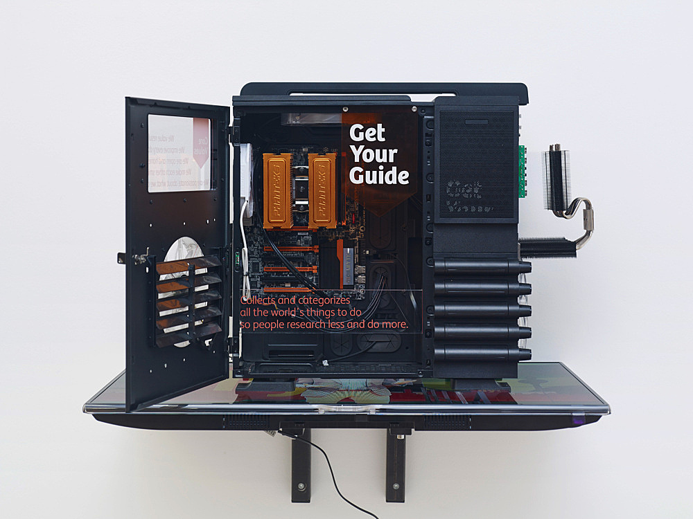 "Simon Denny – ""Berlin Startup Case Mod: GetYourGuide"", 2014 custom computer case, packaging, heavy-duty computer hardware, metal fittings, digital prints on custom plexiglas components, Samsung UE40F6500 SS, video on USB stick 87 x 91 x 54 cm"