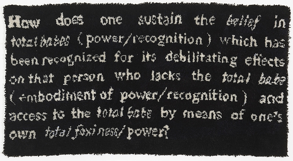 """Frances Stark – """"How does one sustain the belief in total babes (power/recognition) which has been recognized for its debilitating effects on that person who lacks the total babe (embodiment of power/recognition) and access to the total babe by means of one's own total foxiness/ power?"""", 1991 hook rug 97 x 186 x 4 cm"""