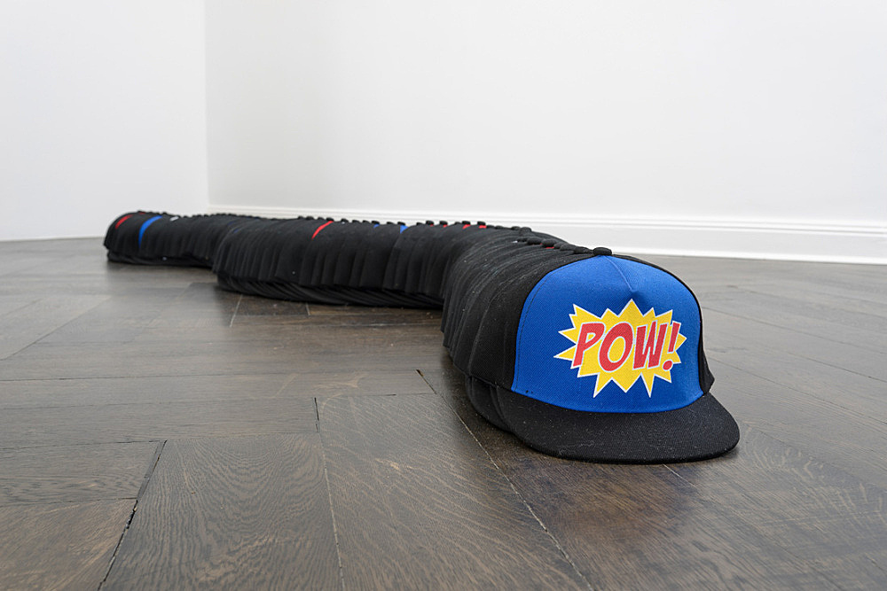 Lutz Bacher – Wham, 2016 102 baseball hats dimensions variable dimensions installed: 11,5 x 20 x 310 cm installation view Galerie Buchholz, Berlin 2016