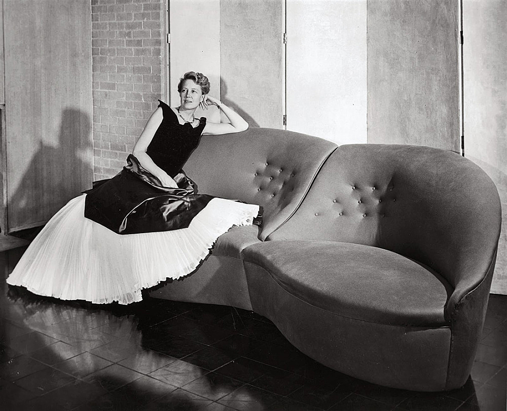 – Dominique de Menil wearing a 1949 Charles James evening gown, seated on the Butterfly Sofa James designed for her living room photograph by F. Wilbur Seiders, ca. 1951