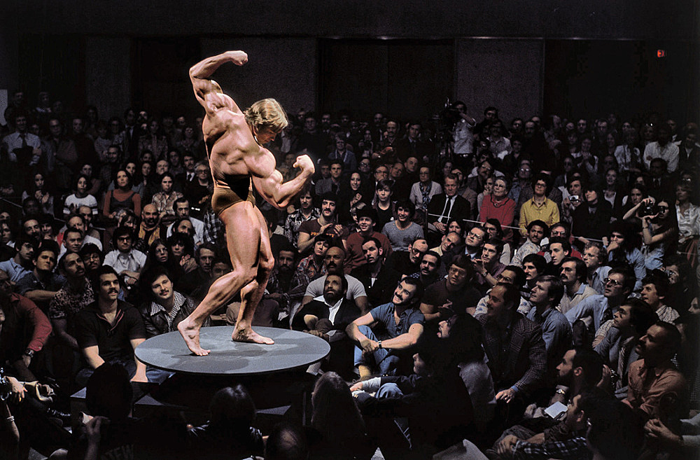 Eliott Erwitt – Arnold Schwarzenegger during the performance series Articulate Muscle: The Male Body in Art at the Whitney Museum, New York City, 25 February 1976