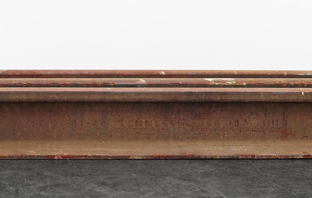 Cameron Rowland – Norfolk Southern (Tennessee), 2017 Steel relay rail 18 x 489 x 73 cm Relay rail is rail that has been removed from its original line and resold. Relay rail was first sold by railroad companies to mining companies for pit railways. Steel rail is made using coal and iron ore. In the late 1860s, the Alabama and Chattanooga Railroad; the Georgia and Alabama Railroad; the Selma, Rome and Dalton Railroad; and the Macon and Brunswick Railroad were constructed using convict lease labor. By 1895 all of these lines had been consolidated into Southern Railway, which built hubs in Birmingham, Chattanooga, and Atlanta, allowing it to transport coal and iron ore throughout the Southeast. In 1982, Southern Railway merged with Norfolk and Western Railway to create Norfolk Southern. This Norfolk Southern relay rail was used in the Tennessee section of the system.