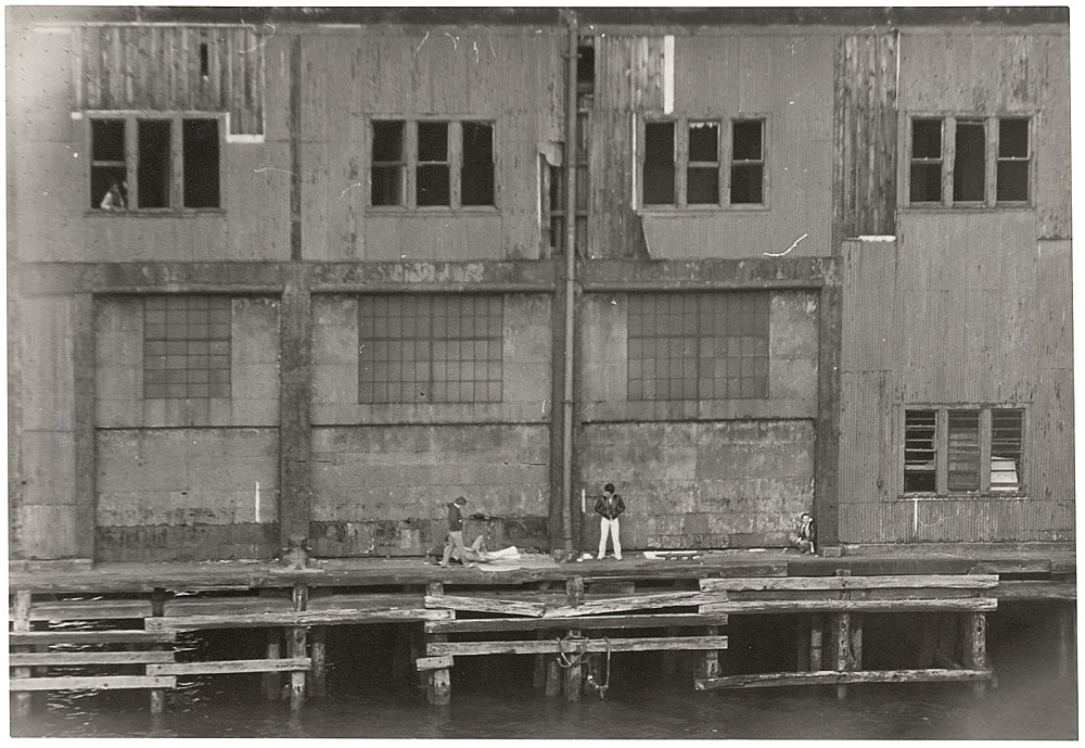 Alvin Baltrop – The Piers (exterior with four figures), n.d. (1975-1986) silver gelatin print image size: 15.9 x 23.5 cm paper size: 15.9 x 23.5 cm (framed: 35.3 x 40.4 x 2.8 cm)