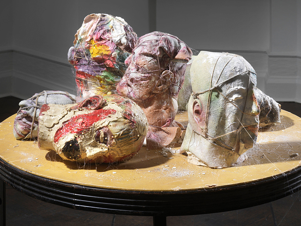 """Richard Hawkins – """"The Garden of Loved Ones"""", 2018 rubber masks, clay, plaster, twine on card table 101.6 x 91.44 x 91.44 cm detail"""