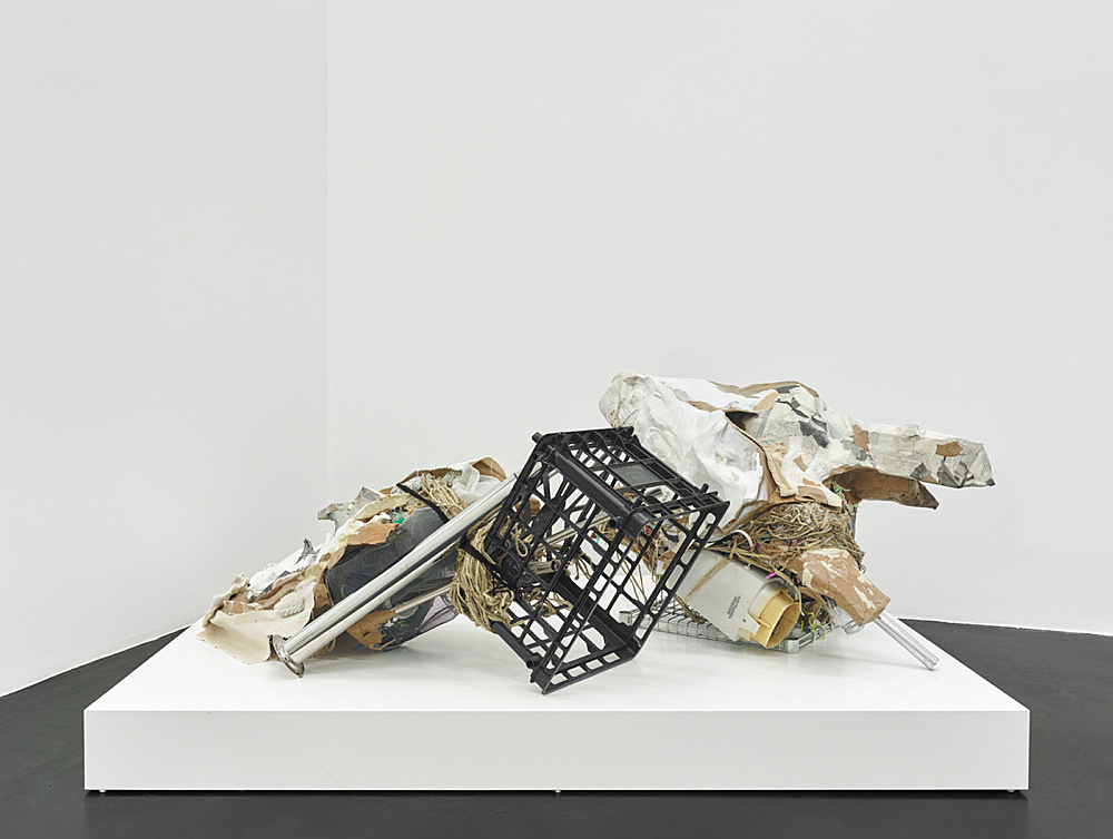 """Danica Barboza – """"Interposition 007th : Hupnos — Pompē"""", 2019 Hand modeled clay, paper, polyvinyl acetate, metal pale, plastic shipping crate, metal table leg, rope, canvas, chenille, mixed media Sculpture 63 x 177 x 103 cm Plinth 15 x 124 x 172.5 cm"""